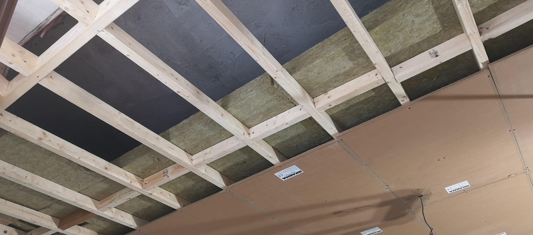 image of some ceiling joists with heavy acoustic insulation and soundproof board