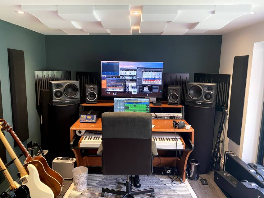 The inside of a home music studio designed by City Insulation. A mixing desk fully setup with keyboard, speakers and lots of acoustic treatment around the room